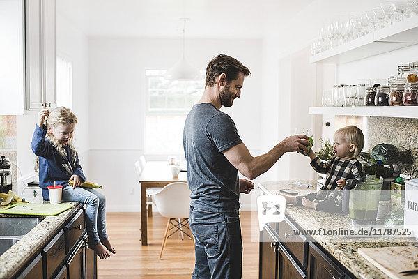Mädchen sieht Vater beim Füttern der Schwester in der Küche zu Hause an