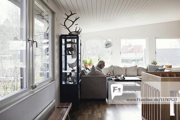 Volle Länge des älteren Mannes  der auf dem Sofa im Wohnzimmer zu Hause sitzt.