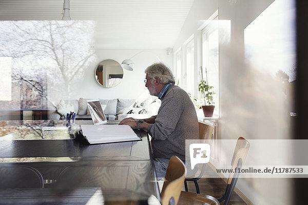 Senior Mann mit Laptop beim Sitzen am Tisch durchs Fenster gesehen
