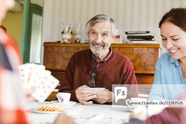 Lächelnder älterer Mann  der mit seiner Familie zu Hause Karten spielt.