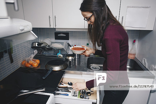 Seitenansicht der Frau  die den Löffel aus der Schublade in der Küche pflückt.