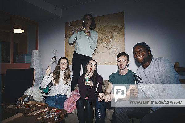 Porträt fröhlicher junger Freunde auf Sofa gegen Weltkarte im Studentenwohnheim