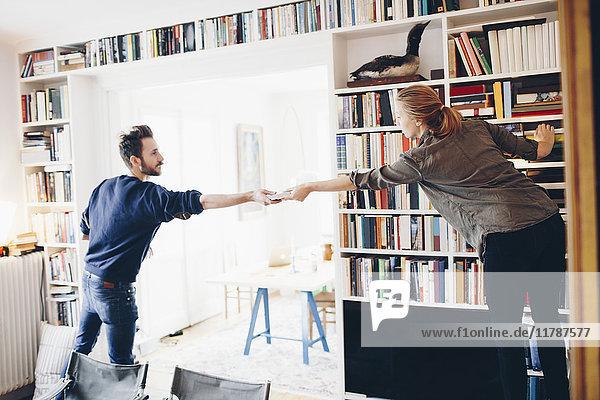 Rückansicht des Mannes  der der Frau ein Buch schenkt  das gegen das Bücherregal zu Hause steht.