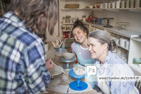 Fröhliche Töpferinnen beim Anblick eines reifen Kollegen mit Handwerkzeug in der Keramikwerkstatt