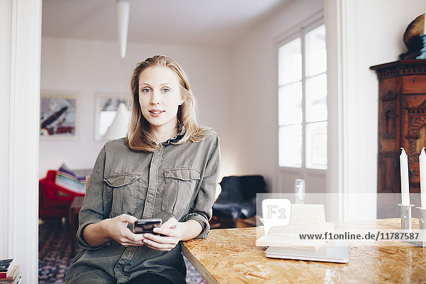 Portrait of young woman using mobile phone sitting by table at home