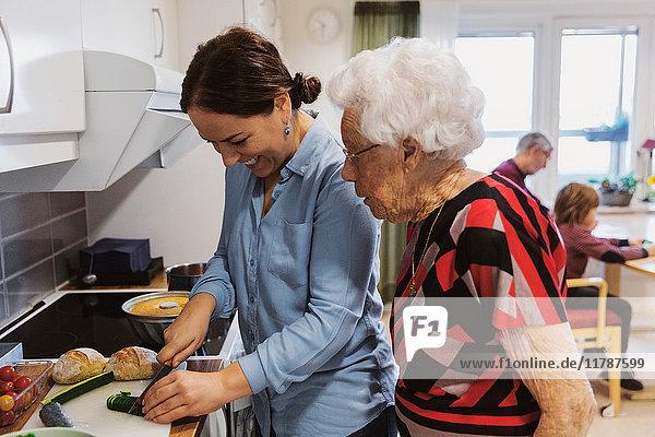 Seitenansicht der Seniorin beim Anblick der Tochter  die in der Küche Zucchini schneidet.
