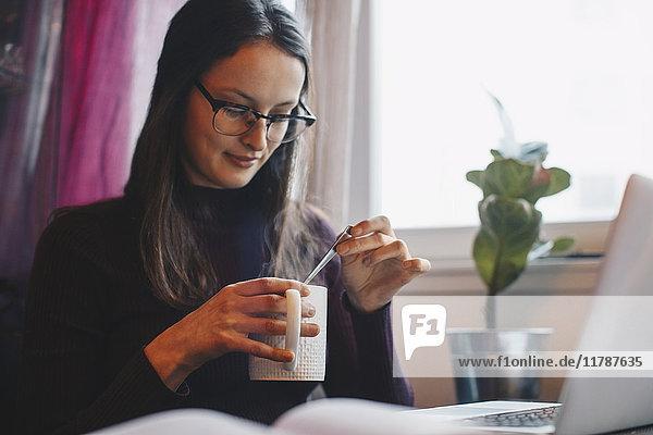 Junge Frau hält Kaffeetasse mit Laptop und Buch auf dem Tisch im Studentenwohnheim