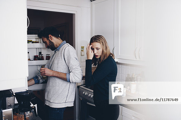Mann und Frau stehen in der Küche zu Hause