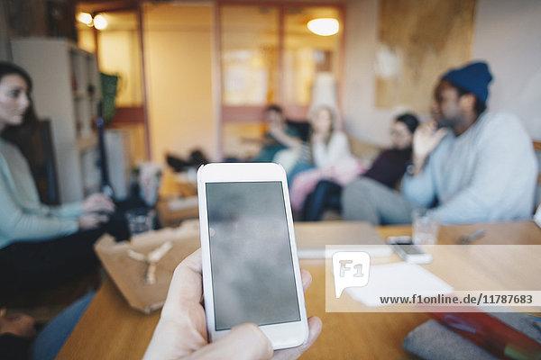 Gestutzte Hand Frau mit Handy gegen Freunde im Studentenwohnheim Zimmer