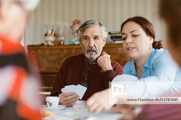 Senior Mann spielt Karten mit der Familie zu Hause
