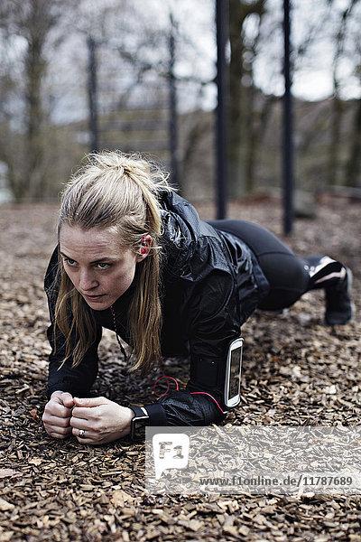 Ermittelte Athletin  die eine Bretterstellung im Wald durchführt.