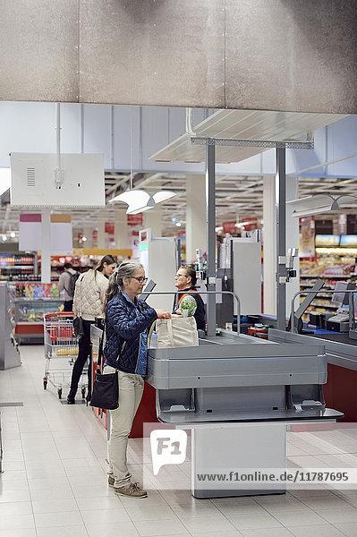Frau mit Einkaufstasche an der Kasse im Supermarkt