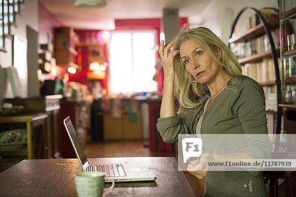 Reife Frau schaut abgelenkt weg  während sie den Laptop zu Hause benutzt.