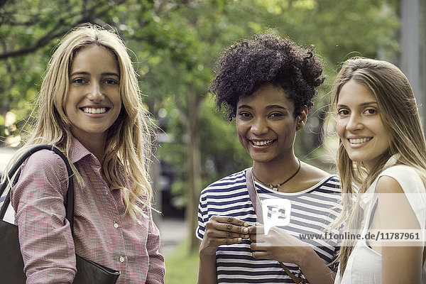 Junge Frauen lächeln gemeinsam im Freien  Porträt