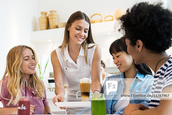 Young women having drinks together in cafe