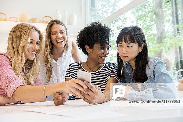 Junge Frauen lachen über Multimedia-Smartphone im Café