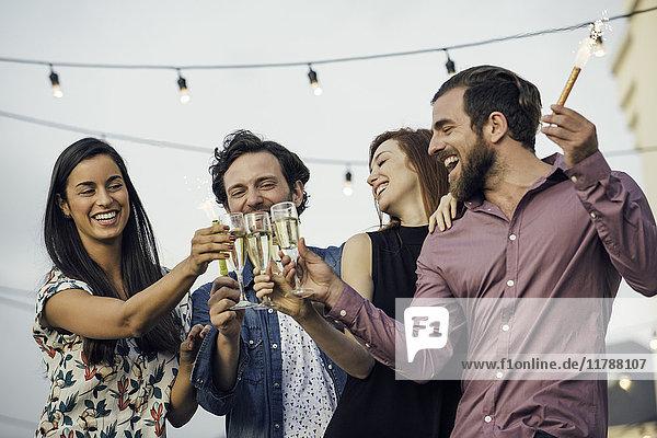 Freunde klirren an Champagnergläsern im Freien.