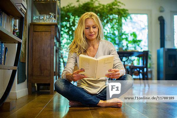 Reife Frau sitzt zu Hause auf dem Boden,  liest Buch