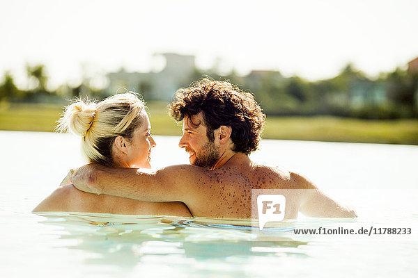 Paare  die sich im Wasser entspannen und sich gegenseitig in die Augen schauen.