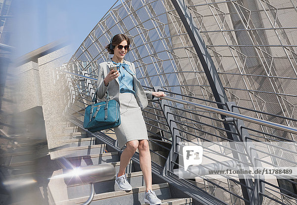 Geschäftsfrau in Sportschuhen mit Handy und Kopfhörer über sonnige Stadttreppe