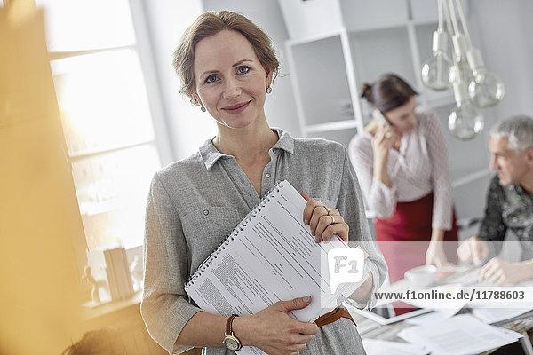 Portrait lächelnde Geschäftsfrau mit Papierkram in der Bürobesprechung