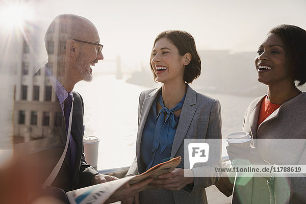 Silhouettierte Geschäftsleute lachend  Kaffee trinkend und Zeitung lesend auf sonniger Stadtbrücke