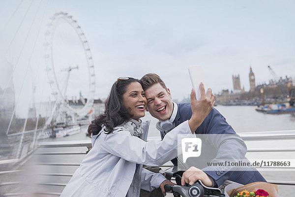 Lächelndes Paar Touristen  die Selfie mit Fotohandy auf der Brücke in der Nähe von Millennium Wheel  London  UK nehmen
