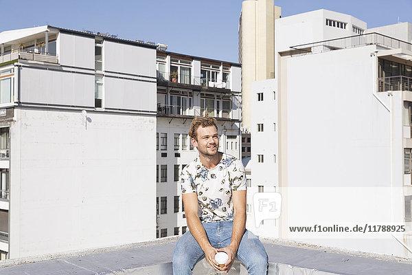 Junger Mann beim Kaffeetrinken auf der Dachterrasse