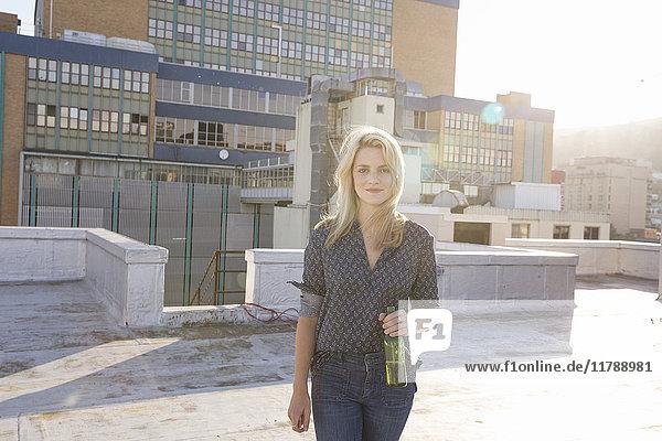 Junge Frau trinkt Bier auf der Dachterrasse