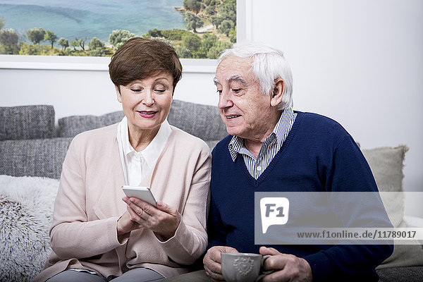 Senior couple lying on couch using smartphone