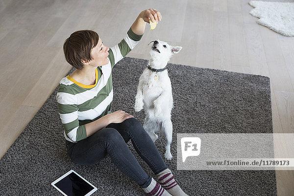 Frau sitzt mit ihrem Hund auf dem Boden im Wohnzimmer.