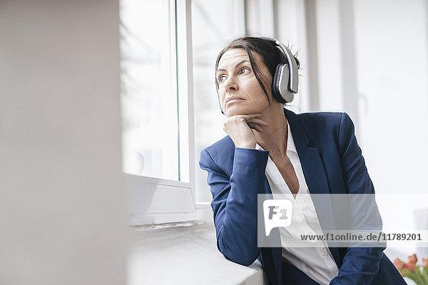 Porträt einer Frau  die aus dem Fenster schaut  während sie über Kopfhörer Musik hört.