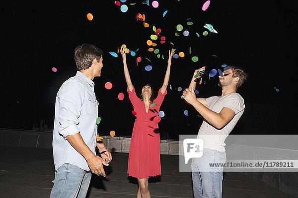 Junge Leute feiern eine Dachparty  schmeißen Konfetti.