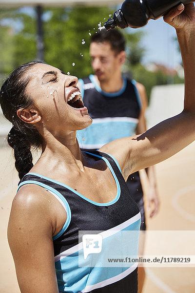 Passende Frau  die Wasser auf ihr Gesicht spritzt.
