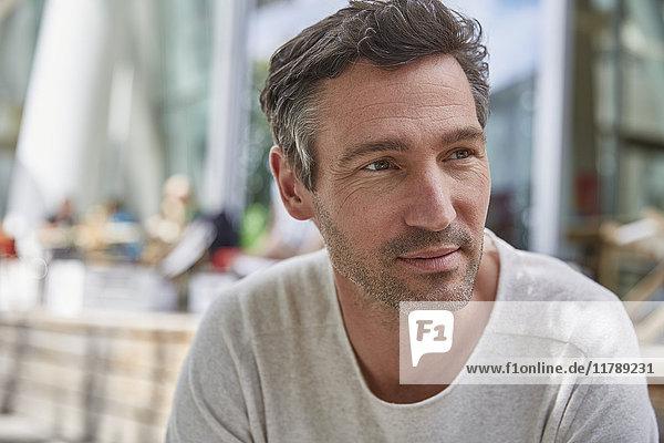 Porträt eines Mannes in einem Außencafé