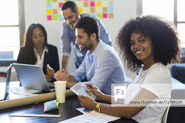 Porträt einer lächelnden Geschäftsfrau bei einer Besprechung im Büro