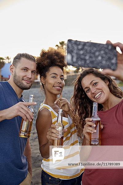 Drei Freunde mit Bierflaschen  die Selfie am Strand mitnehmen.