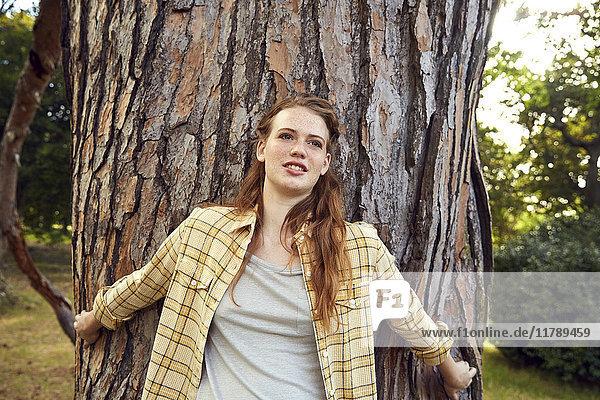 Bildnis einer jungen Frau  die sich an den Baumstamm lehnt