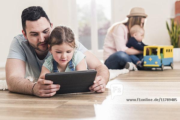 Vater und Tochter mit Tablette im neuen Zuhause mit Frau und Baby im Hintergrund
