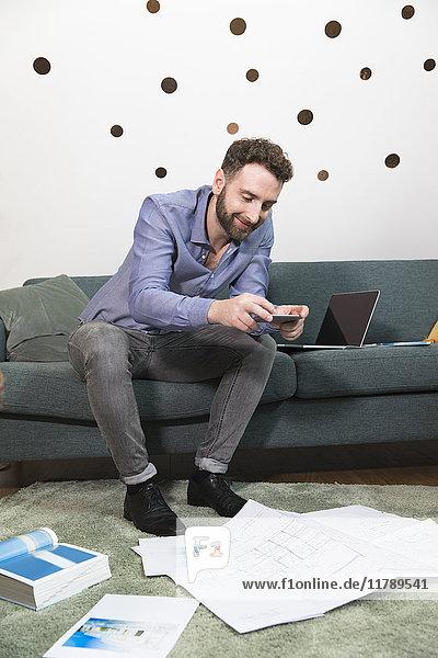 Mann fotografiert Blaupause im modernen Büro