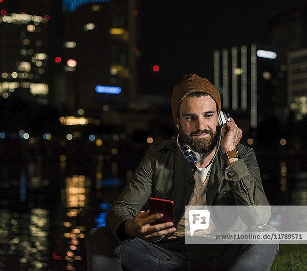 Stilvoller junger Mann mit Handy und Kopfhörer  der nachts am städtischen Flussufer sitzt.