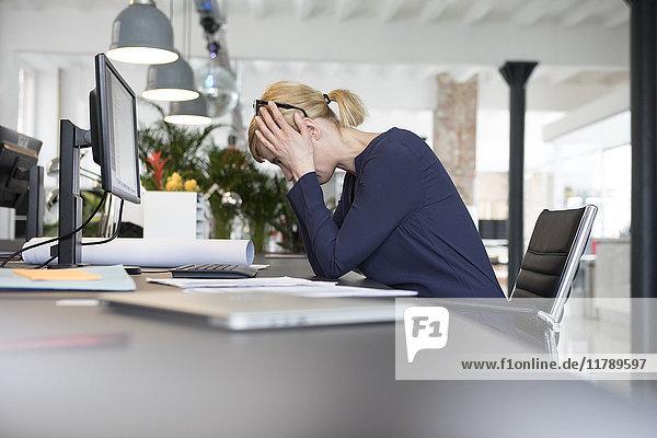 Geschäftsfrau  die im Büro arbeitet und gestresst ist.