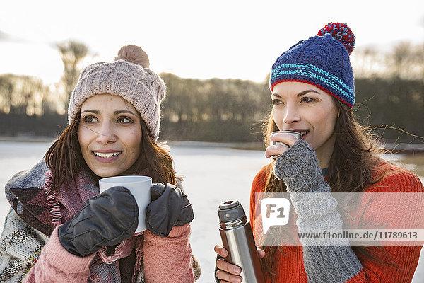 Zwei Frauen trinken im Winter heiße Getränke im Freien.