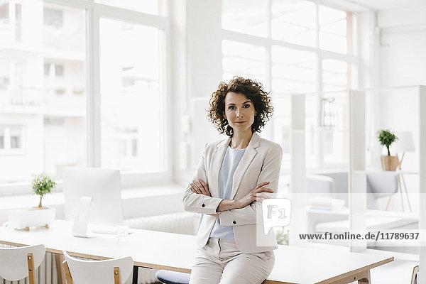 Geschäftsfrau im Büro sitzend auf dem Schreibtisch mit gekreuzten Armen