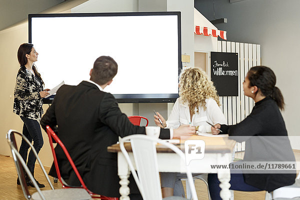 Frau leitet Präsentation im Büro auf Großbildleinwand