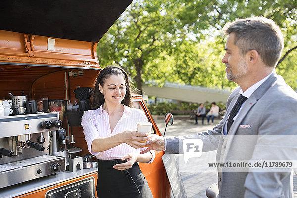 Geschäftsmann  der Kaffee zum Mitnehmen auf der Straße kauft.