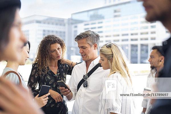Gruppe von gelegentlichen Geschäftsleuten  die sich das Handy auf dem Stadtplatz anschauen.