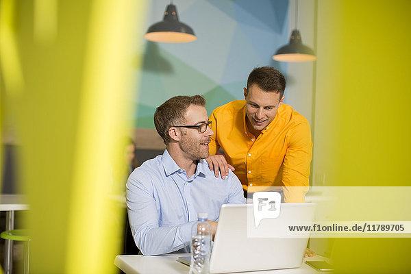 Zwei Geschäftsleute mit Laptop sprechen in der Bürolounge