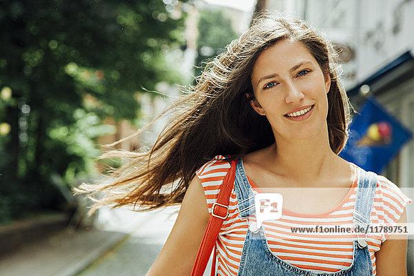 Porträt einer lächelnden jungen Frau in der Stadt