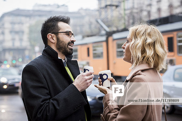Geschäftsmann und Geschäftsfrau mit Kaffee zum Mitnehmen in der Stadt